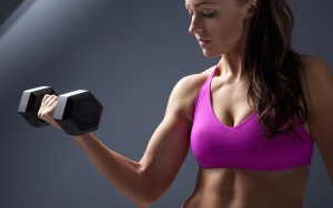 Studio photo of attractive young woman lifting dumbbell.; Shutterstock ID 96921779; PO: aol; Job: production; Client: drone